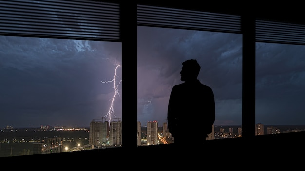 O homem solitário em pé perto da janela no fundo chuvoso