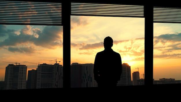 O homem solitário em pé perto da janela no meio urbano