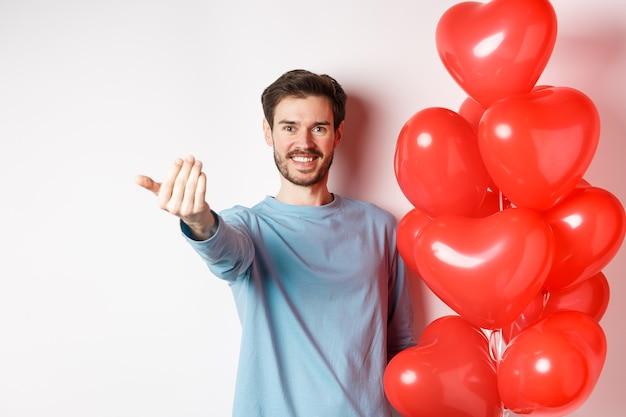 O homem sorridente acena para você se aproximar, siga-me o gesto, provocando seu amante para seguir em frente, tenha uma surpresa romântica, em pé perto do balão vermelho no dia dos namorados, fundo branco.