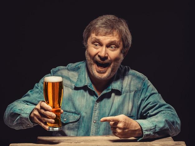 O homem sorridente na camisa jeans com copo de cerveja
