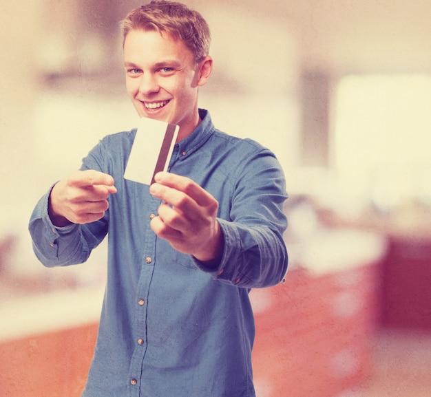 O homem sorrindo e apontando para um cartão de crédito