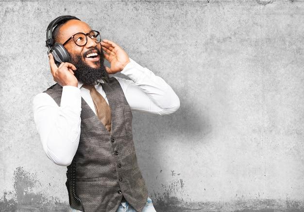 O homem sorrindo e ouvindo música com fones de ouvido