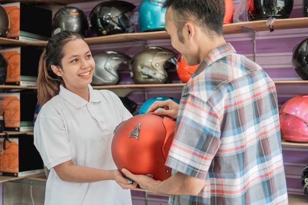O homem sorriu ao escolher um capacete servido por uma lojista asiática na loja de capacetes