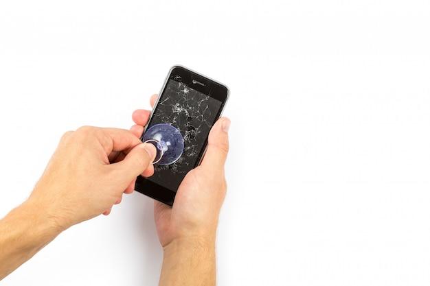 O homem substituindo o protetor de tela de vidro temperado quebrado para smartphone