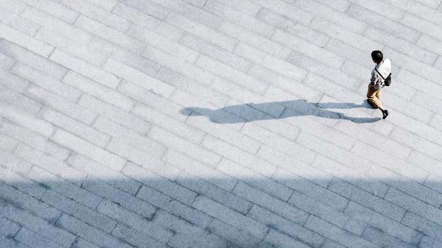 O homem superior da vista aérea anda sobre através do concreto pedestre com silhueta preta.