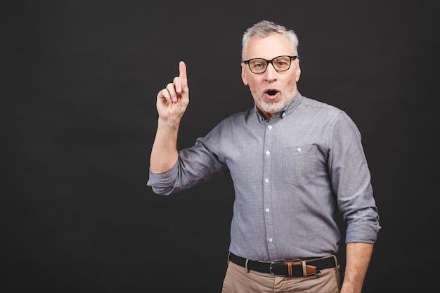 O homem superior envelhecido que veste os vidros isolados contra o fundo preto surpreendeu e sorrindo ao apresentar com a mão e apontar com o dedo.