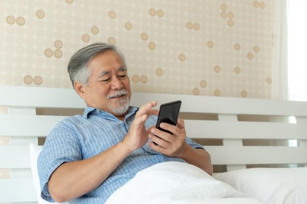 O homem superior que usa um smartphone, sorrindo sente feliz na cama em casa.