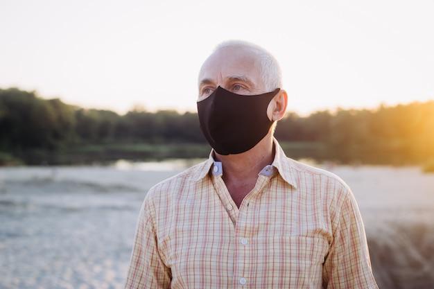 O homem superior veste a máscara protetora contra doenças infecciosas e gripe, conceito dos cuidados médicos. quarentena do coronavírus.