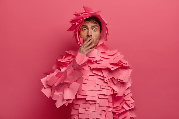 O homem surpreso cobre a boca e encara com olhos arregalados, receios de alguma coisa, ouve notícias surpreendentes, suspira com rumores chocantes, usa notas adesivas, isoladas na parede rosa. conceito omg