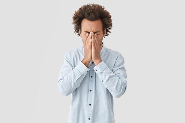 O homem tem cabelo encaracolado, cobre o rosto com as palmas das mãos, tenta reunir os pensamentos e se concentrar, fica envergonhado