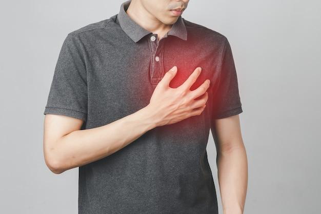 O homem tem dor no peito, sofre de doenças cardíacas, doenças cardiovasculares, ataque cardíaco. conceito de cuidados de saúde.