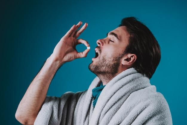 O homem tem o frio, comendo os comprimidos isolados no fundo azul.