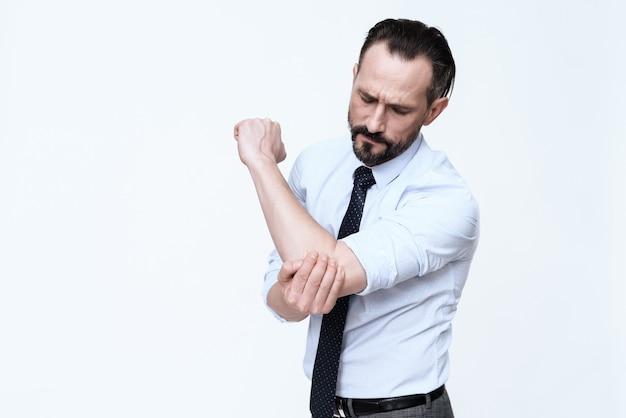 O homem tem um cotovelo dolorido. dói ele, ele sofre.
