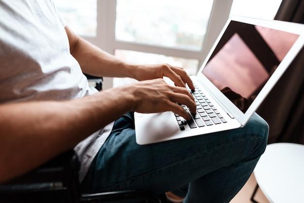 O homem tem um laptop no colo, para o qual ele trabalha