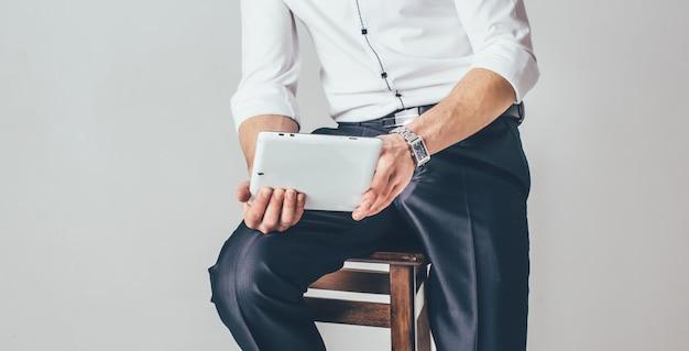 O homem tem um tablet nas mãos. ele se senta em uma cadeira vestido com uma camisa branca e calça chique