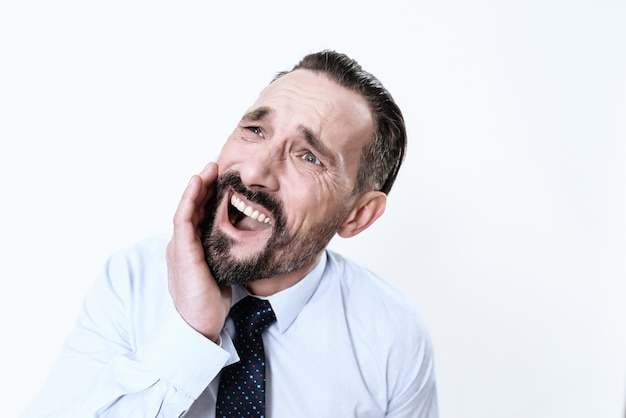 O homem tem uma dor de dente. ele segura as mãos na mandíbula.
