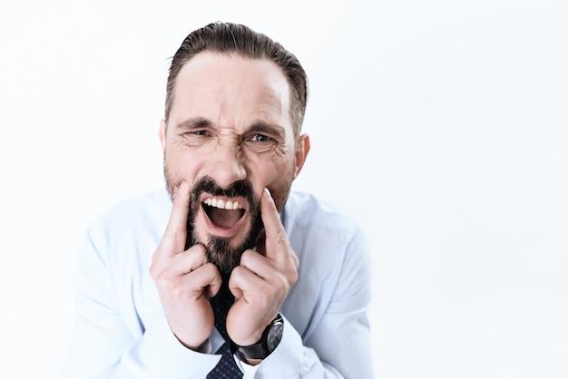 O homem tem uma dor de dente ele segura as mãos na mandíbula