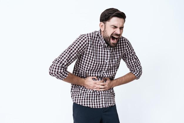O homem tem uma dor de estômago ele segura as mãos no estômago