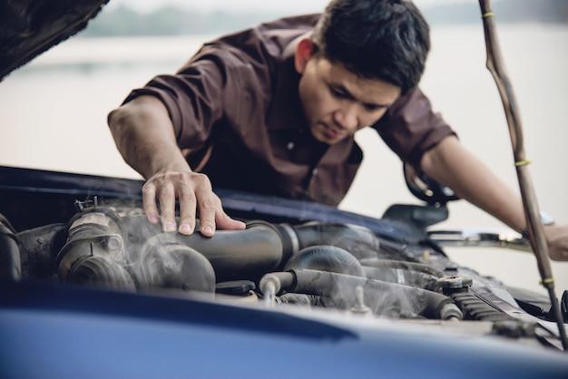 O homem tenta consertar um problema de motor de carro em uma estrada local