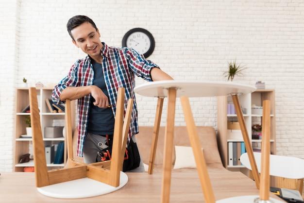 O homem tenta dobrar sua mesa de café e fezes.