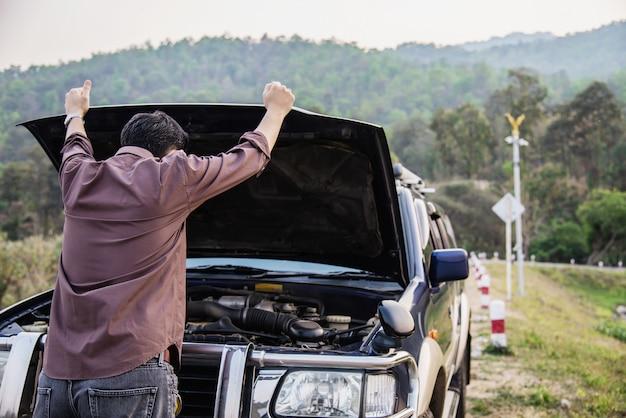 O homem tenta reparar um problema do motor de carro em uma estrada local chiang mai tailândia