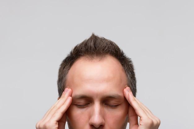 O homem tenta se concentrar, reunir-se com pensamentos, meditando e massageando suas têmporas