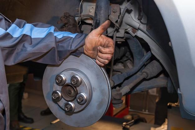 O homem terminou de consertar o freio a disco. reparo do freio a disco.