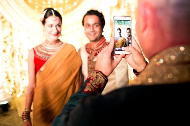 O homem tira foto do casal de casamento hindu no smartphone