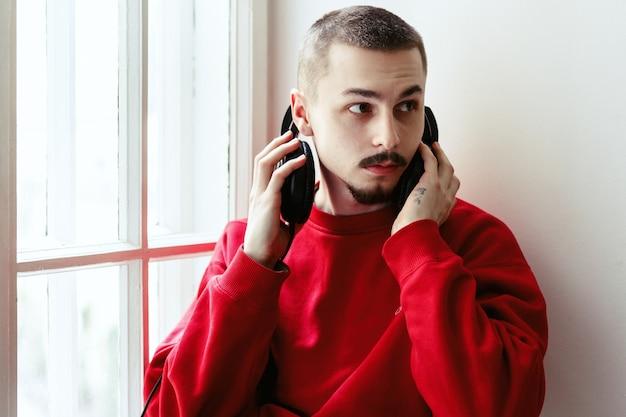 O homem tira o fone de ouvido sentado no peitorel da janela