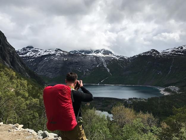 O homem tira uma foto da deslumbrante paisagem escandinava