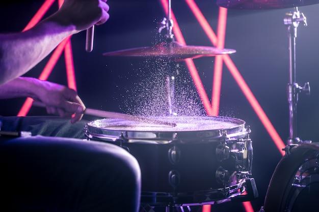 O homem toca bateria, no fundo de luzes coloridas