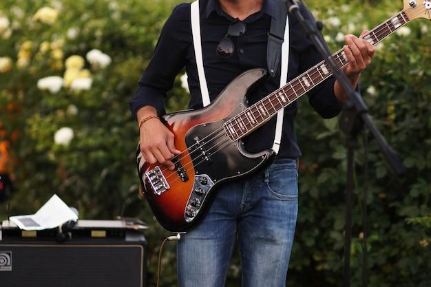 O homem toca uma guitarra no jardim