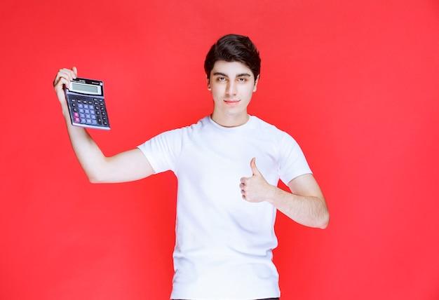 O homem trabalhou na calculadora e parece satisfeito com o resultado.