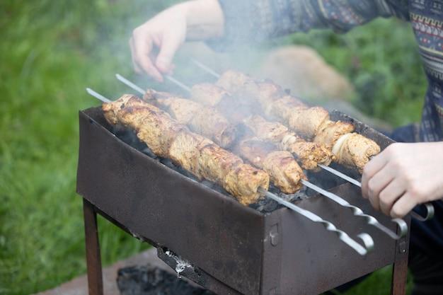 O homem transforma suculentas fatias de carne em espetos em uma churrasqueira aberta