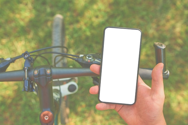 O homem treina na bicicleta com smartphone