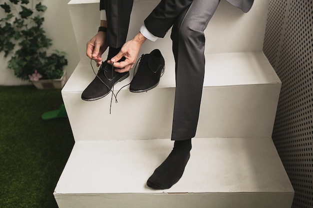O homem, um homem de negócios, um empresário ou o noivo senta-se em uma escada branca e um novo negócio de sapatos de camurça preta amarrar cadarço, close-up. o conceito de negócios, empreendedorismo, moda.