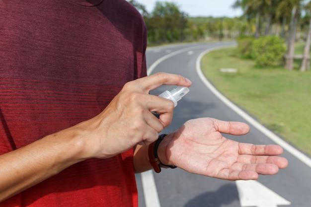 O homem usa álcool para limpar as mãos para prevenção do surto do vírus coronavírus. coivd 19