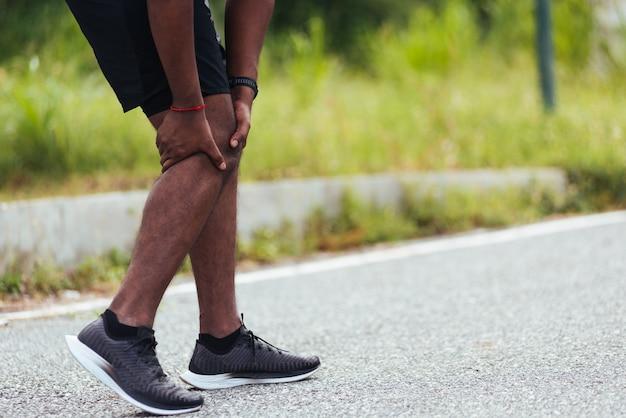 O homem usa as mãos segurando em sua dor no joelho enquanto corre