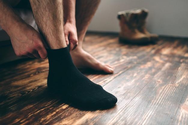 O homem usa meias pretas. estilo masculino.