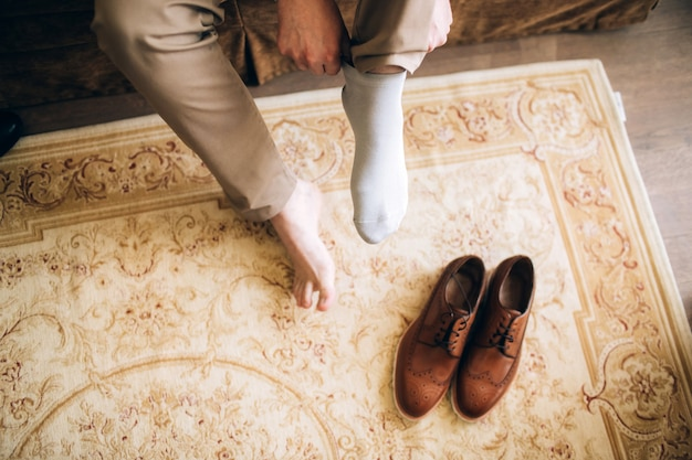 O homem usa sapatos. amarre os cadarços nos sapatos. estilo masculino. profissões. para se preparar para o trabalho, para a reunião.