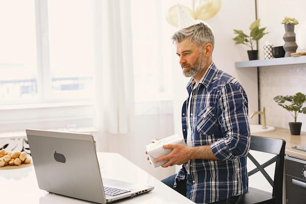O homem usa um chapéu de festa. o homem mantém uma caixa com um presente. homem tem uma chamada por meio de seu laptop.