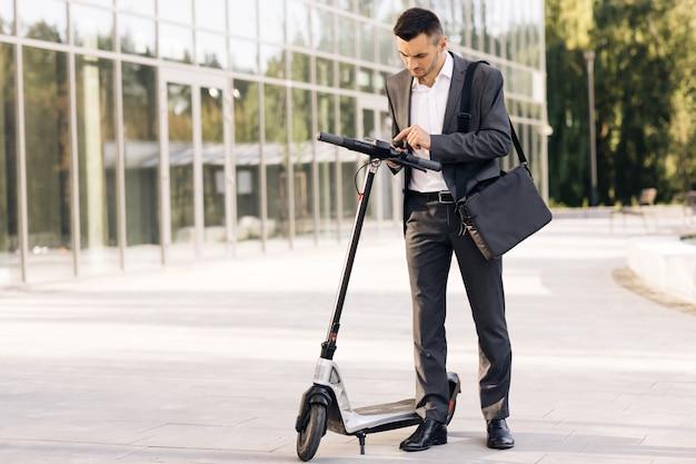 O homem usa uma scooter elétrica como meio de transporte moderno na cidade um aplicativo de homem de negócios