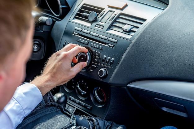 O homem vai dirigir, procurando uma música legal