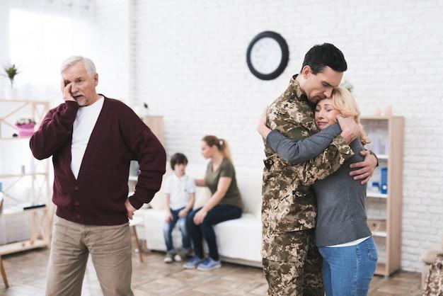 O homem vai para o serviço militar. ele se despede de sua família.