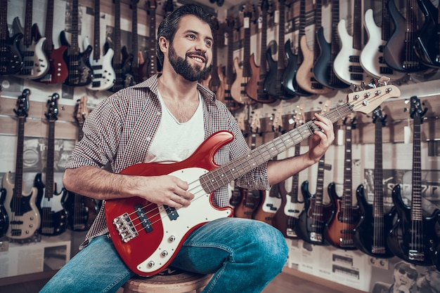 O homem verifica a guitarra elétrica na loja do instrumento musical.