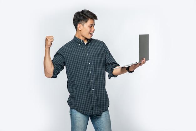 O homem vestia camisa branca e calça escura, segurando um laptop e fingindo estar feliz