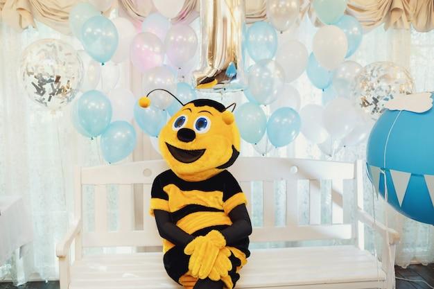 O homem vestido como uma abelha senta no banco