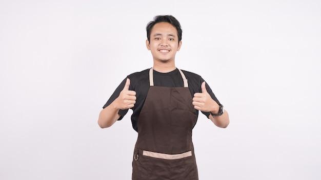 O homem vestindo o avental fica em um fundo branco isolado com um gesto de ok Foto Premium