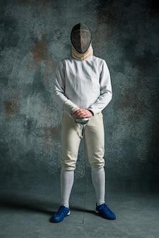 O homem vestindo terno de esgrima com espada contra cinza