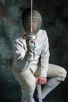 O homem vestindo terno de esgrima com espada
